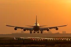 Det enorma flygplanet landar under soluppgång Royaltyfria Bilder