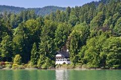 Det ensamma huset på bergsjön Arkivbild