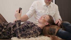 Det europeiska unga lyckliga paret kopplar av hemma och att ligga på golvet Flicka som ligger på varven av en grabb med en telefo lager videofilmer