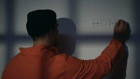 Det fängslade manliga skrivande hemmet på cellväggen som känner sig hemsjuk, hoppas för frihet arkivfilmer