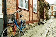 Det färgrika cykelanseendet mot en vägg av en gammal halva timrade ho Arkivbilder