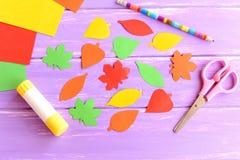 Det färgrika sidasnittet från kulört papper, sax, limpinnen, blyertspennan, papper täcker på purpurfärgad träbakgrund Top beskåda Royaltyfria Foton