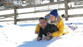 Det förälskade barnparet ligger i en vitt snö och krama Skratta har det lyckliga folket rolig det fria i varm vinter arkivfilmer