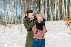 Det förälskade härliga unga paret går parkerar på en klar solig vinterdag royaltyfria bilder