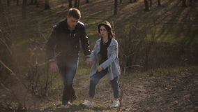 Det förälskade paret går i skogen på solnedgången arkivfilmer