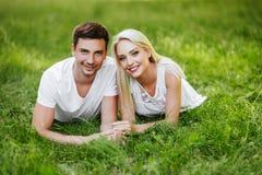 Det förälskade sammanträdet för älskvärda par på grönt gräs arkivbild