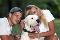 Det förälskade unga paret kopplar av i natur med deras hund arkivfoton
