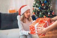 Det förbluffade barnet rymmer närvarande och ser det Hon håller munnen öppnad Flickan bär julhatten Vuxna människan stöttar henne arkivbilder