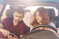 Det förbryllade paret sitter i bil, den skäggiga mannen rymmer den smarta telefonen, använder online-översikter, försök att finna royaltyfri bild