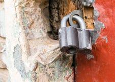 Det försåg med gångjärn stora låset stänger dörrnärbilden mot en bruten bakgrund för stenvägg, grungebakgrund Royaltyfria Bilder