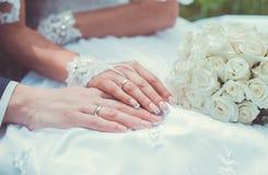 Det försiktiga handlaget av händer av nygifta personer Arkivfoton