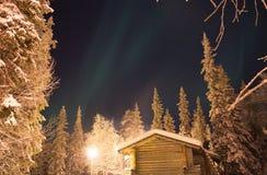 Det första tecknet av nordliga ljus ovanför den sörjaträden och kabinen Arkivbild