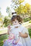 Det förtjusande barnet behandla som ett barn flickan som spelar med, behandla som ett barn - dockan och vagnen Royaltyfri Bild