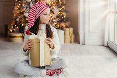 Det förtjusande kvinnliga barnet bär den Santa Claus hatten, varm kläder, den håll slågna in gåvaasken, sitter mot dekorerat träd royaltyfria bilder