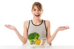 det förvånade barnet bantar kvinnan med broccoli som täckas, i att mäta bandet i bunke Royaltyfria Bilder