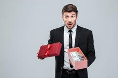 Det förvånade unga affärsmaninnehavet öppnade gåvaasken med pengar Royaltyfri Foto
