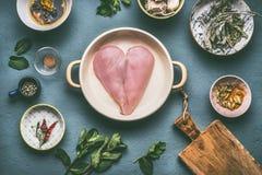Det fega bröstet i hjärtaform i kruka med matlagningingredienser bowlar på grå bakgrund, bästa sikt arkivfoto