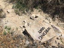 Det fel vägtecknet valt omkull på jordningen royaltyfri fotografi