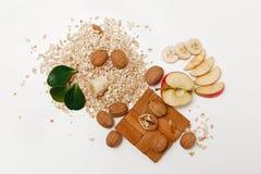 Det finns bananen, Apple med valnötter och rullande havre, träställ, med gröna sidor, sund ny organisk mat på den vita Backgren Royaltyfria Foton
