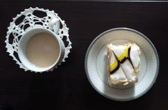 Det finns en kopp med cappuccino och en platta med kakan Royaltyfria Bilder