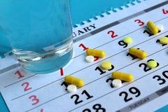Det finns medicin på kalendern varje dag, och det finns ett exponeringsglas av vatten royaltyfri bild