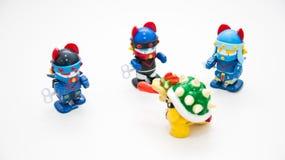 Det finns robotar med tre blåa hjälmar på en vit bakgrund, runt om ett monster med den röda tungan ut royaltyfri fotografi
