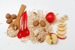 Det finns stycken av banan, Aple, valnötter och trä- och plast-skedar för rullande havre, med gröna sidor, sund ny organisk mat p Arkivfoto