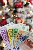 Det fläktade euroet noterar tätt upp julträd i bakgrund Royaltyfria Foton