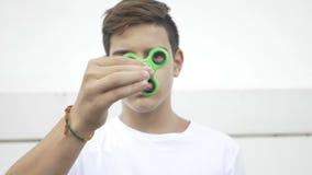 Det fokuserade pojkeinnehavet between fingrar en antistress leksak för rullande rastlös människaspinnare - arkivfilmer