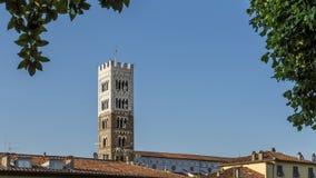 Det forntida klockatornet av domkyrkan av San Martino dyker upp mellan taken av husen i den historiska mitten av Lucca, arkivfoton