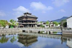 Det forntida trähuset och bron reflekterade i en kanal, Hengdia, Kina Royaltyfria Bilder