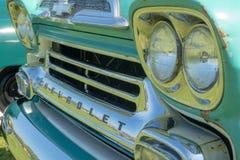 Det främre gallret och ljus på en tappning Chevy åker lastbil Arkivfoton