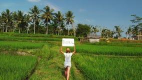 Det fria för ung kvinna med whiteboard- och handskriftordet som är tropiskt på det Surr som flyger längd i fot räknat Grönt ljust arkivfoton