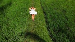 Det fria för ung kvinna med whiteboard- och handskriftordet som är tropiskt på det Surr som flyger längd i fot räknat Grönt ljust royaltyfria bilder