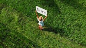 Det fria för ung kvinna med whiteboard- och handskriftordet som är tropiskt på det Surr som flyger längd i fot räknat Grönt ljust royaltyfria foton