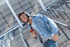 Det friafritid Mulattgrabb i hörlurar som står på trappa med le för musik för smartphone som lyssnande är lyckligt royaltyfri fotografi