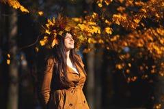 Det frialivsstilslut upp ståenden av den charmiga unga kvinnan som bär en krans av höstsidor gå på hösten fotografering för bildbyråer