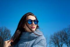 Det frialivsstilslutet upp ståenden av den härliga flickan som går i den snöig vintern, parkerar Le och tycka om vintertid royaltyfri foto