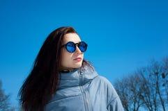 Det frialivsstilslutet upp ståenden av den härliga flickan som går i den snöig vintern, parkerar Le och tycka om vintertid arkivbilder