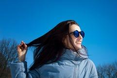 Det frialivsstilslutet upp ståenden av den härliga flickan som går i den snöig vintern, parkerar Le och tycka om vintertid arkivfoton