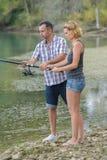 Det fridsamma barnet kopplar ihop fiske vid dammet i höst Arkivfoto