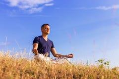 Det fridsamma landskapet av en man som mediterar i lotusblommapositionen Fotografering för Bildbyråer