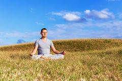 Det fridsamma landskapet av en man som mediterar i lotusblommapositionen Royaltyfri Bild