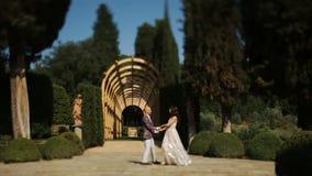 Det frodiga paret dansar i trädgården stock video