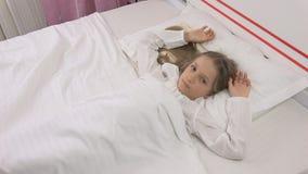 Det fundersamma barnet i säng, den meditativa ungen, flicka kan inte sova i sovrum arkivfoton