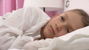 Det fundersamma barnet i säng, den meditativa ungen, liten flicka kan inte sova i sovrum lager videofilmer