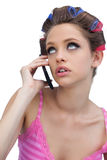 Det fundersamma barnet modellerar bärande hårrullar med telefonen Arkivbild