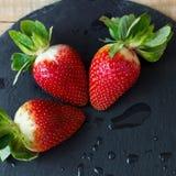 Det fyrkantiga fotoet av tre våta jordgubbar på svart kritiserar plattan Arkivfoto