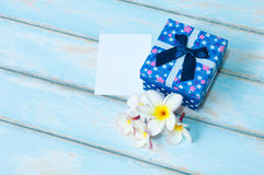 Det gåvaasken och kortet med blomman på himmelblått färgar trägolvet Royaltyfri Foto