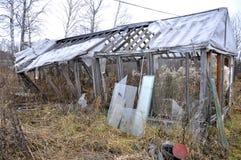 Det gamla brutna träväxthuset i en kökträdgård. Royaltyfria Bilder